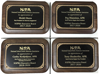 Four plaques of wood and brass to honor outgoing board vice presidents